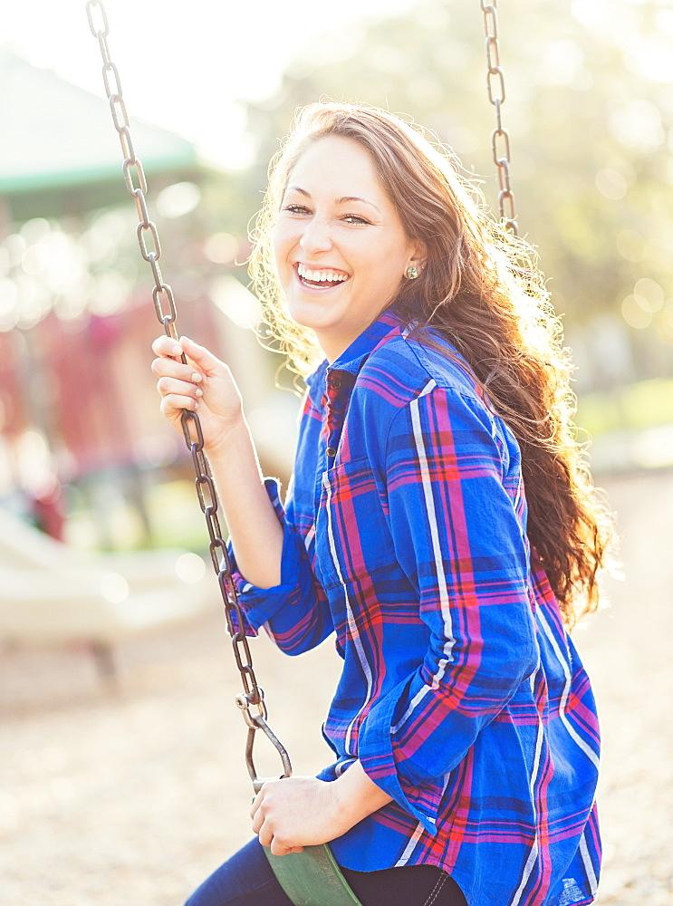 Woman swinging in playground, Jupiter, Florida