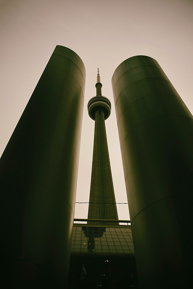 Low angle, symmetrical view of built structure and communications tower, tinted image, Toronto, Canada