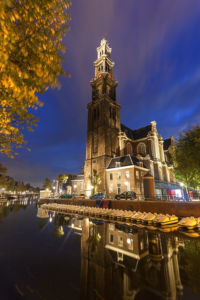 Illuminated Westerkerk Church reflecting in still canal , Westerkerk church, Amsterdam, North Holland, Netherlands