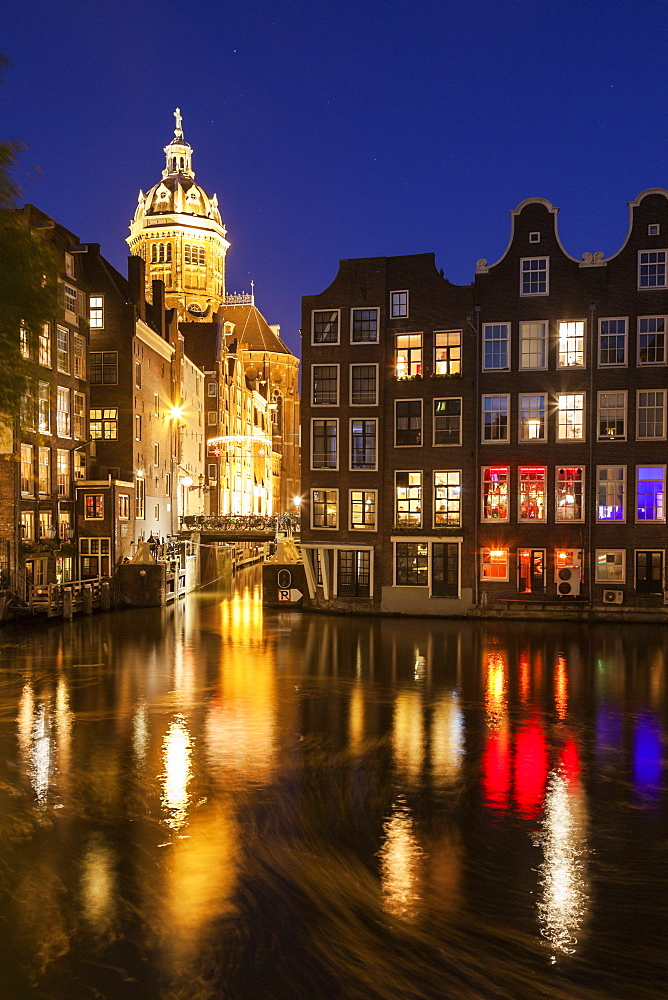 Illuminated buildings by canal at night, Amsterdam, North Holland, Netherlands