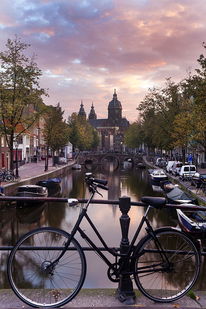 Basilica of st nicholas and bicycle by canal in city, Amsterdam, North Holland, Netherlands