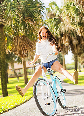 Young woman riding bicycle in park, Jupiter, Florida,USA