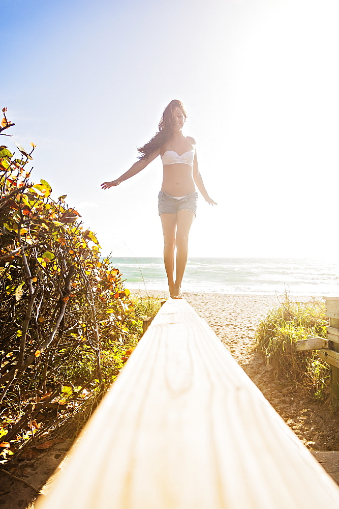 Young woman balancing on boardwalk, Jupiter, Florida,USA