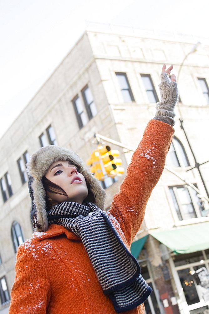Woman calling taxi in winter, Brooklyn, New York,USA