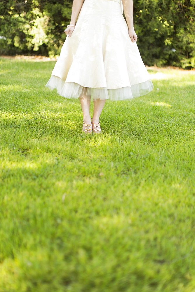 Woman in white dress standing on lawn