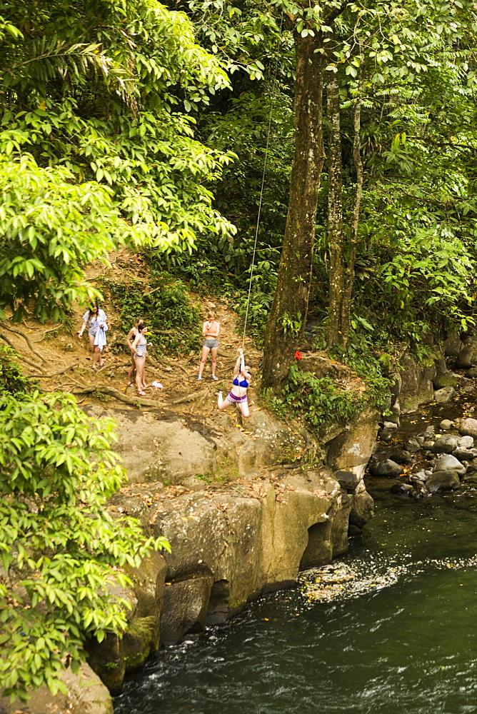 Women swinging on rope swing above river in distance, Costa Rica