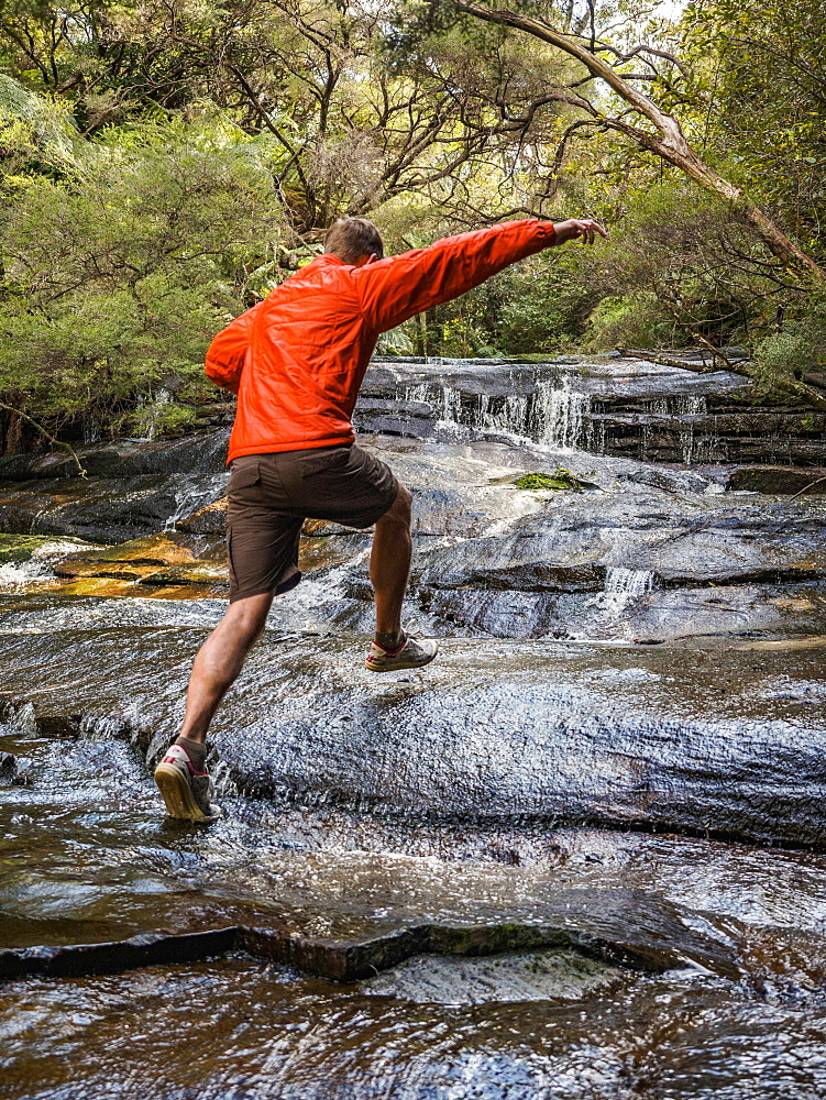 Australia, New South Wales, Katoomba, Man running on rocks of Leura Cascade