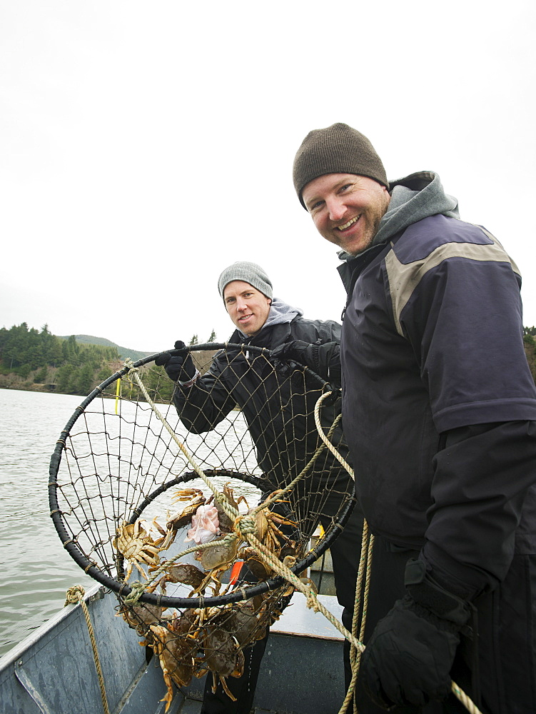 Men showing crabs in net, Rockaway Beach, Oregon