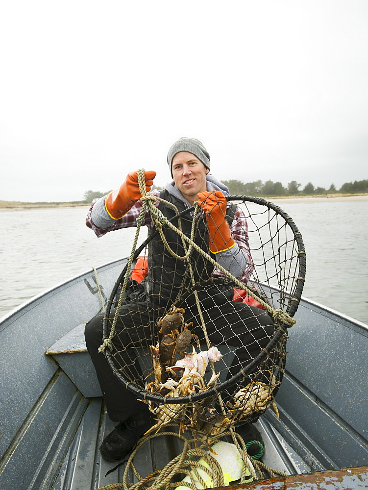 Portrait of man holding crabs in net, Rockaway Beach, Oregon