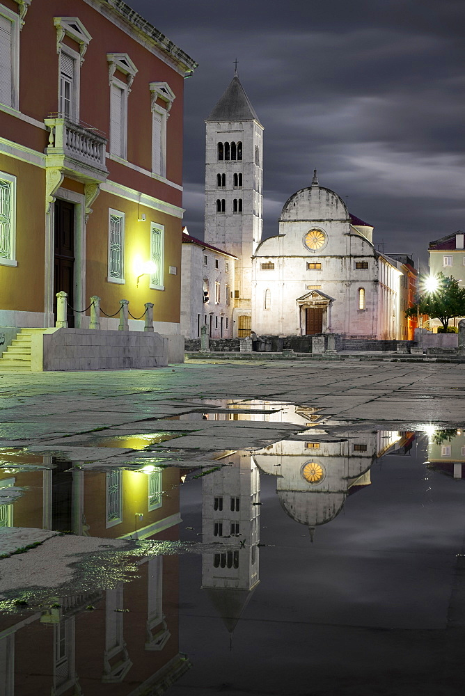 Croatia, Zadar, Buildings reflecting in puddle at dusk