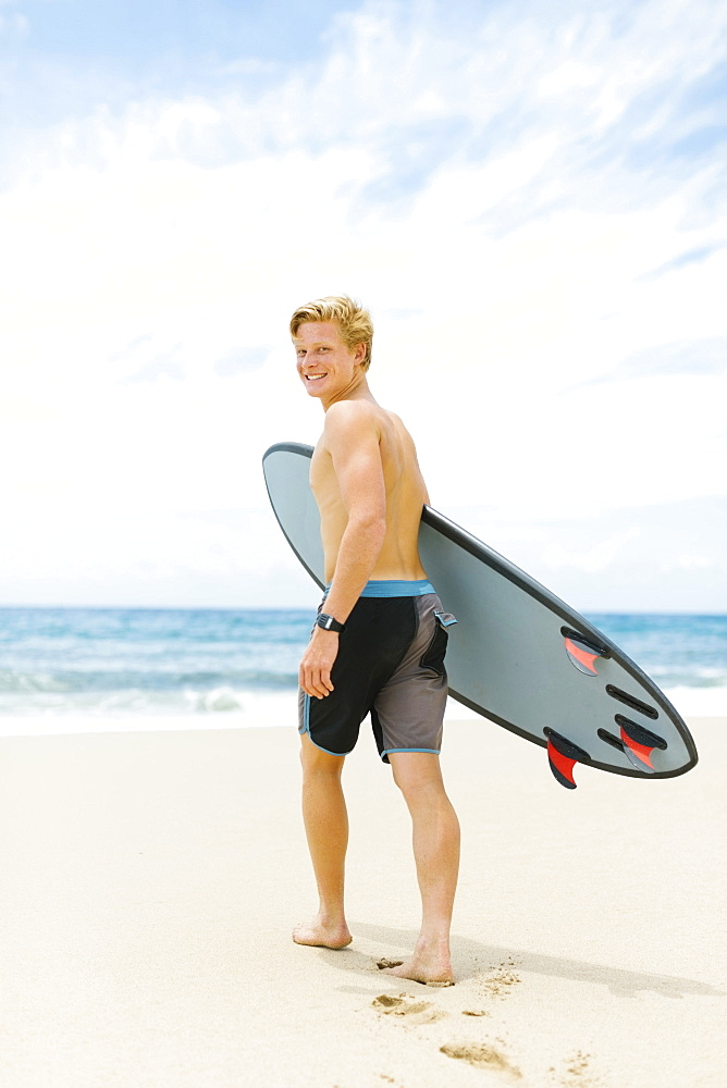 Man walking on beach and holding surfboard