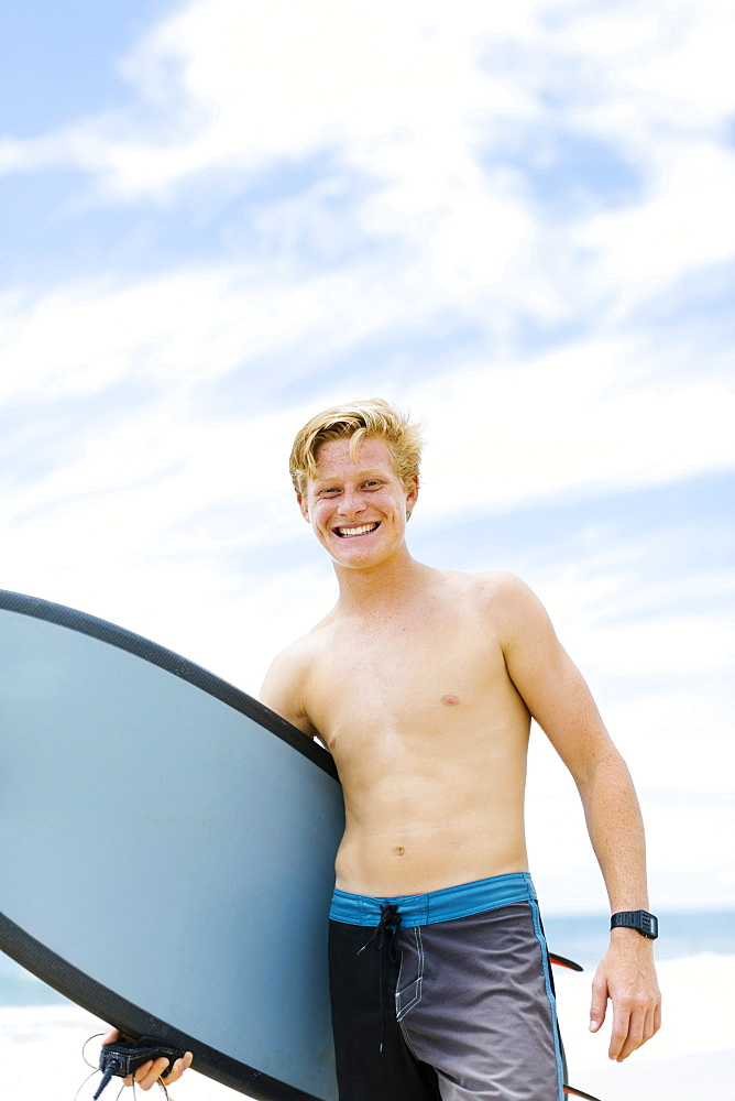 Man standing on beach and holding surfboard