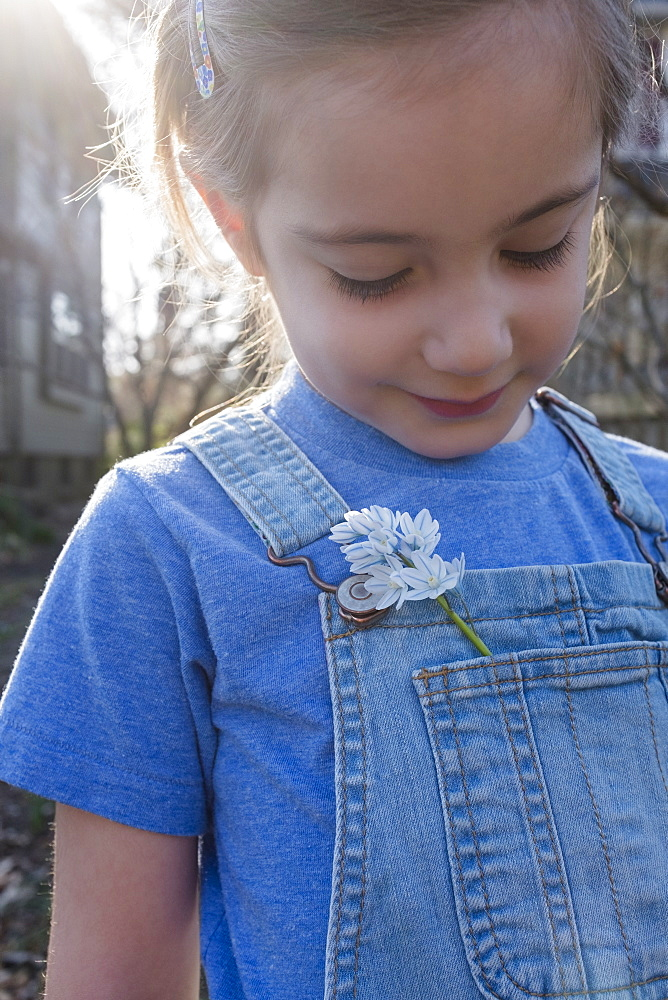 Girl with flower in overalls pocket