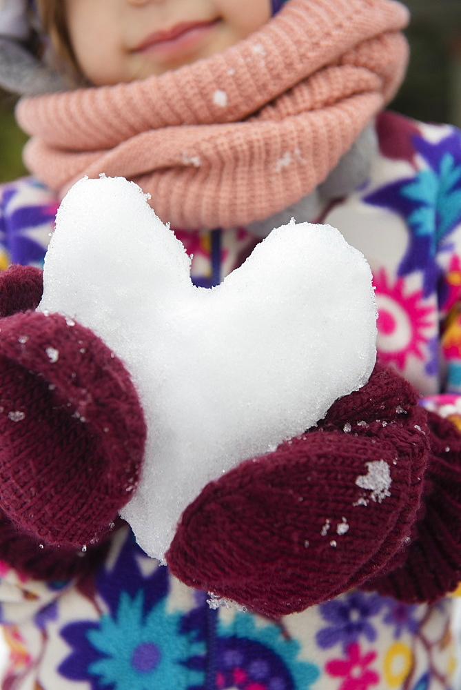 Hands of girl holding snow heart