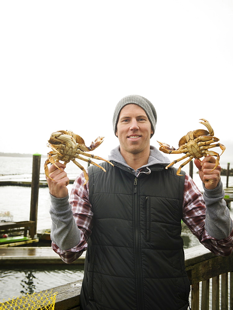 Portrait of man showing crabs, Rockaway Beach, Oregon