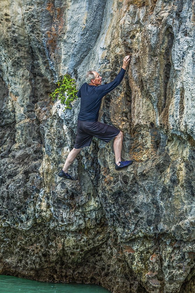 Man rock climbing in Phuket, Thailand