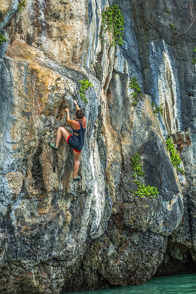 Woman rock climbing in Phuket, Thailand