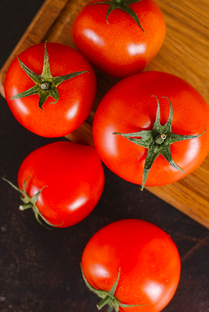 Tomatoes on wooden cutting board