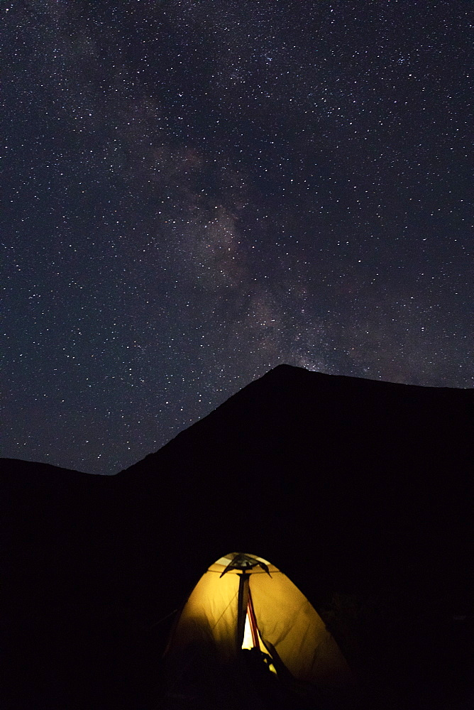 Illuminated tent by mountain at night