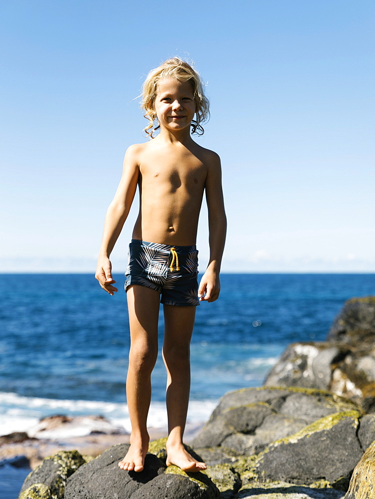 Boy standing on rocks at beach