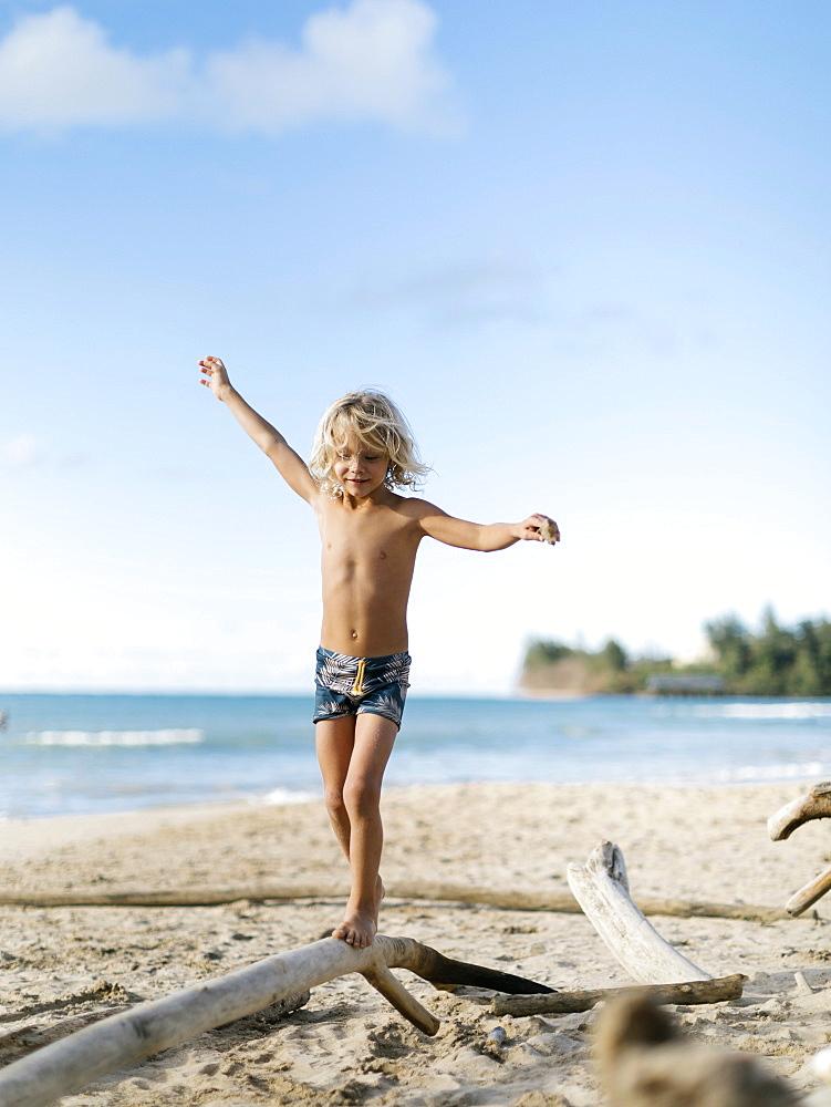 Boy balancing on driftwood