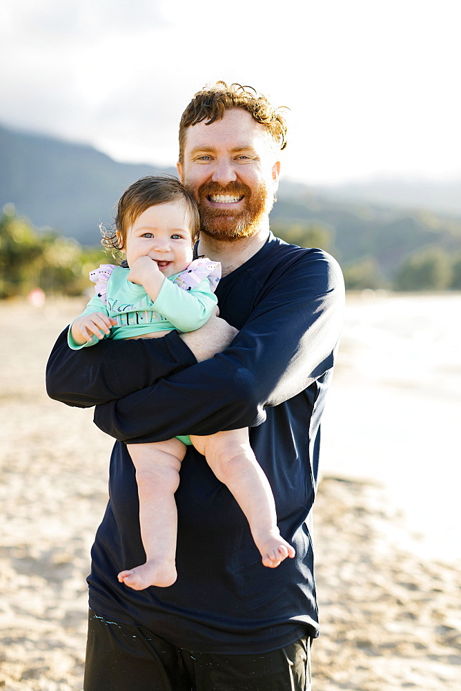 Man holding baby daughter on beach