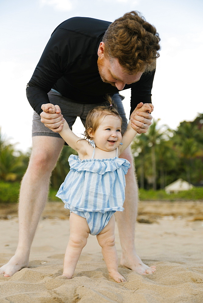 Man playing with baby daughter on beach