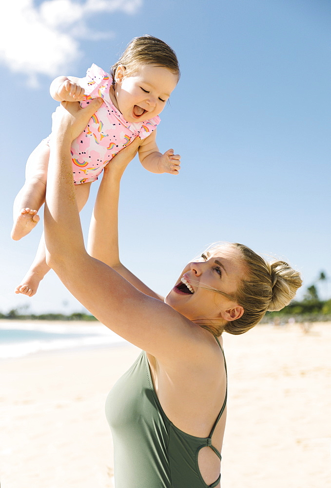 Mother holding her baby girl aloft on beach