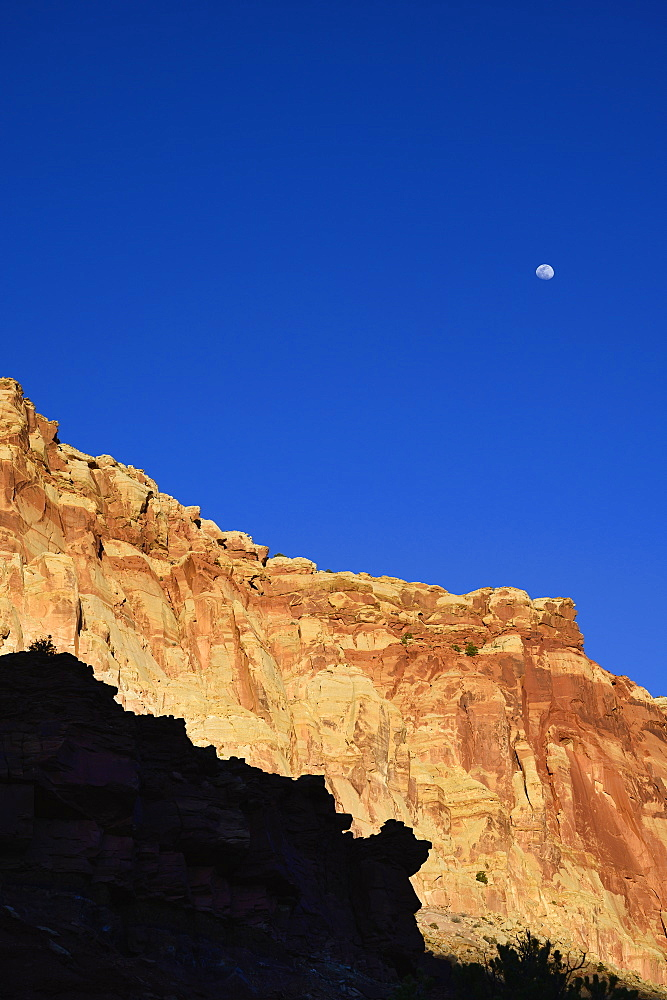 Moon over cliff in shadow in Capitol Reef National Park, USA