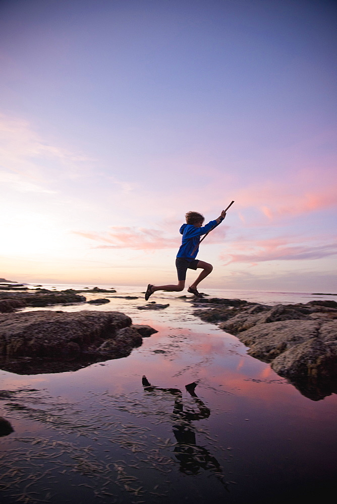 Teenage boy jumping between rocks of tide pool in La Jolla, California