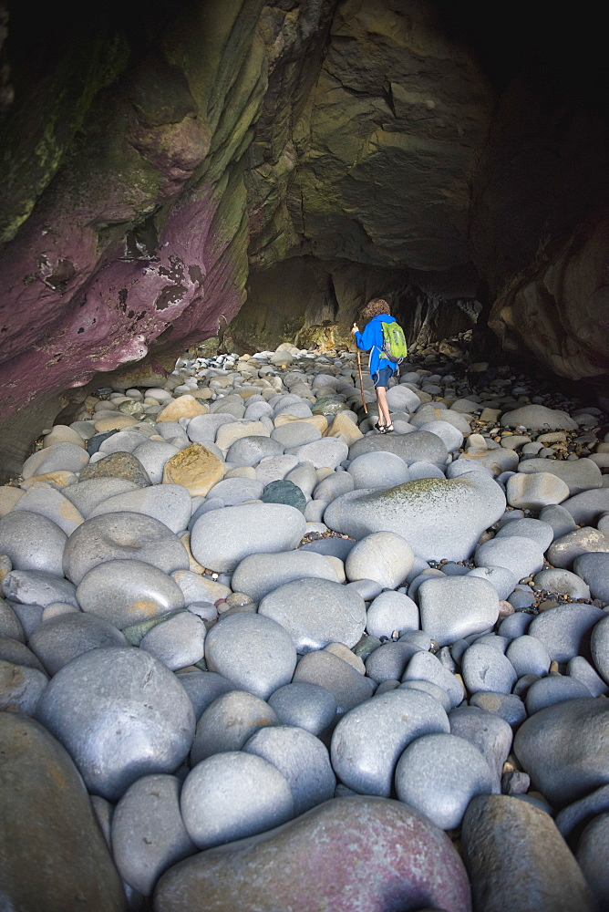 Teenage boy exploring cave with rocks in La Jolla, California