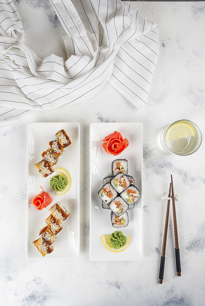 Plates of sushi with chopsticks and drinking glass