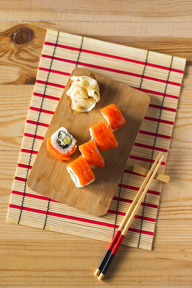 Salmon sushi on cutting board with chopsticks and mat