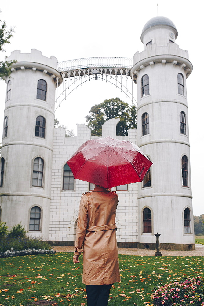 Woman holding red umbrella by Schloss Pfaueninsel in Potsdam, Germany