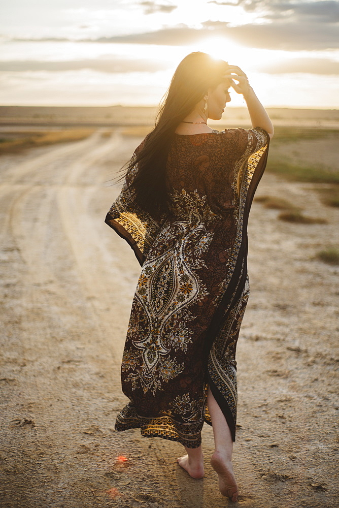Woman wearing patterned dress walking on dirt road at sunset