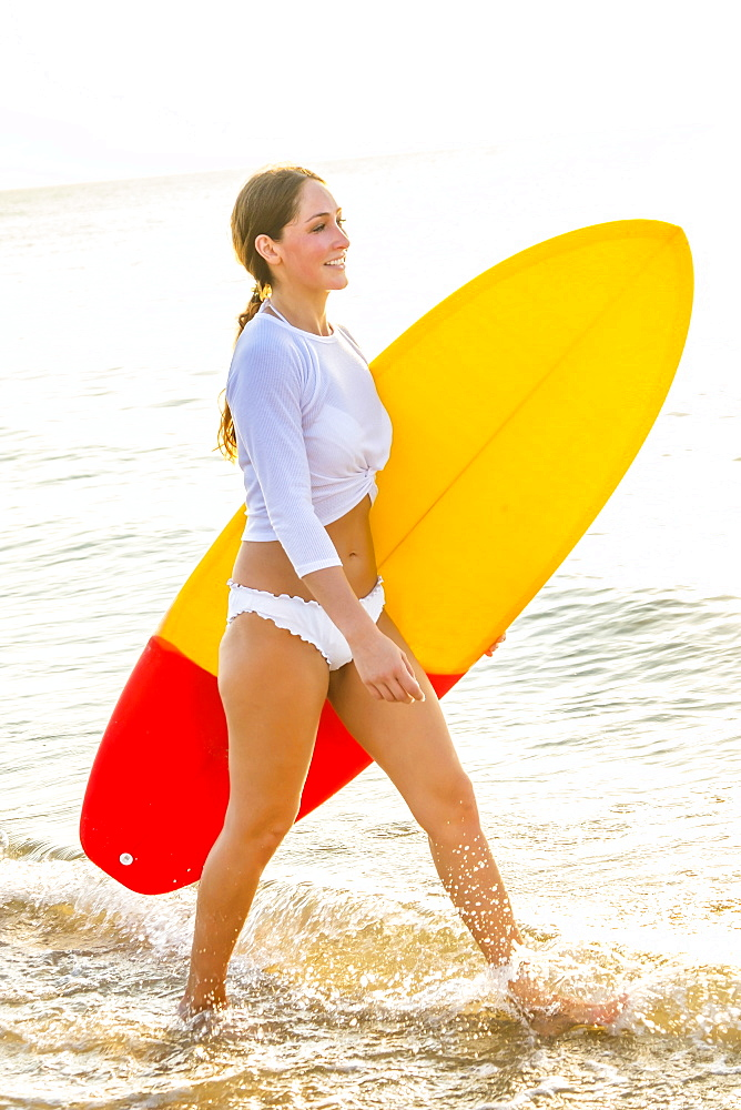 Woman wearing bikini carrying surfboard on beach