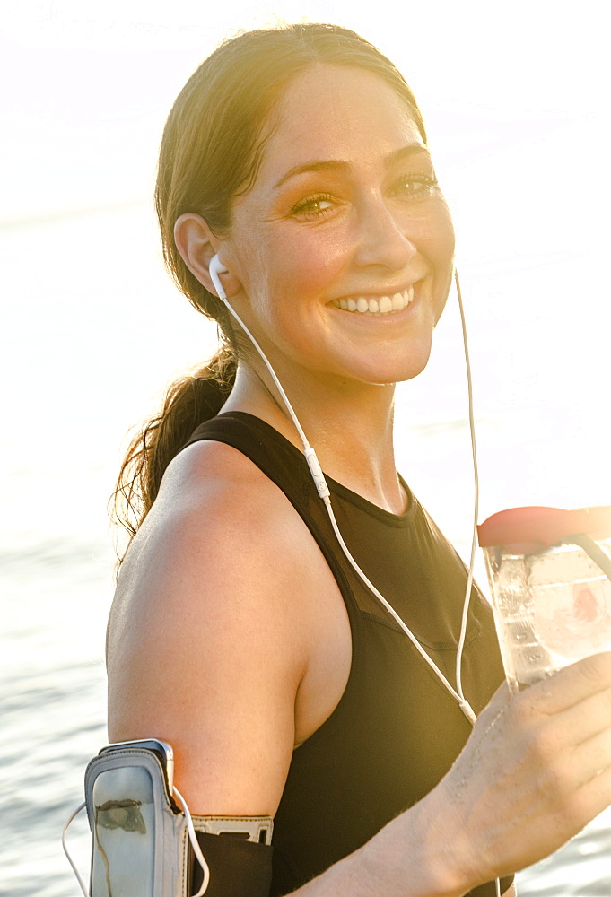 Smiling woman wearing headphones holding water bottle