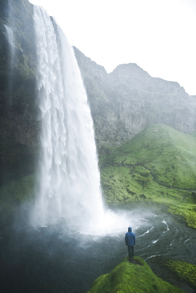 Man standing by Seljalandsfoss waterfall in Iceland