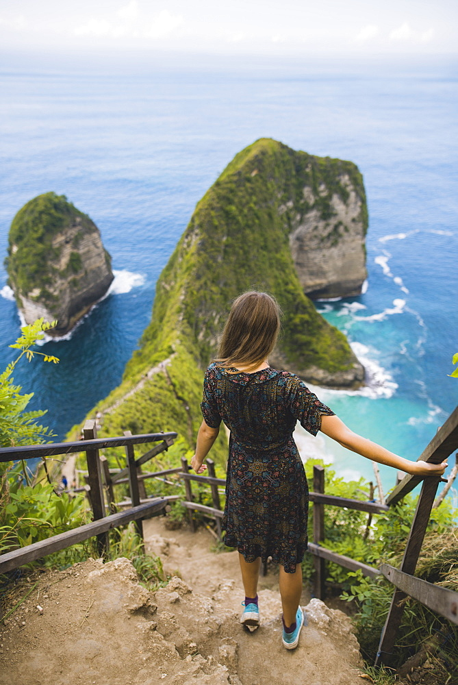 Woman on hillside steps above Kelingking Beach in Nusa Penida, Indonesia