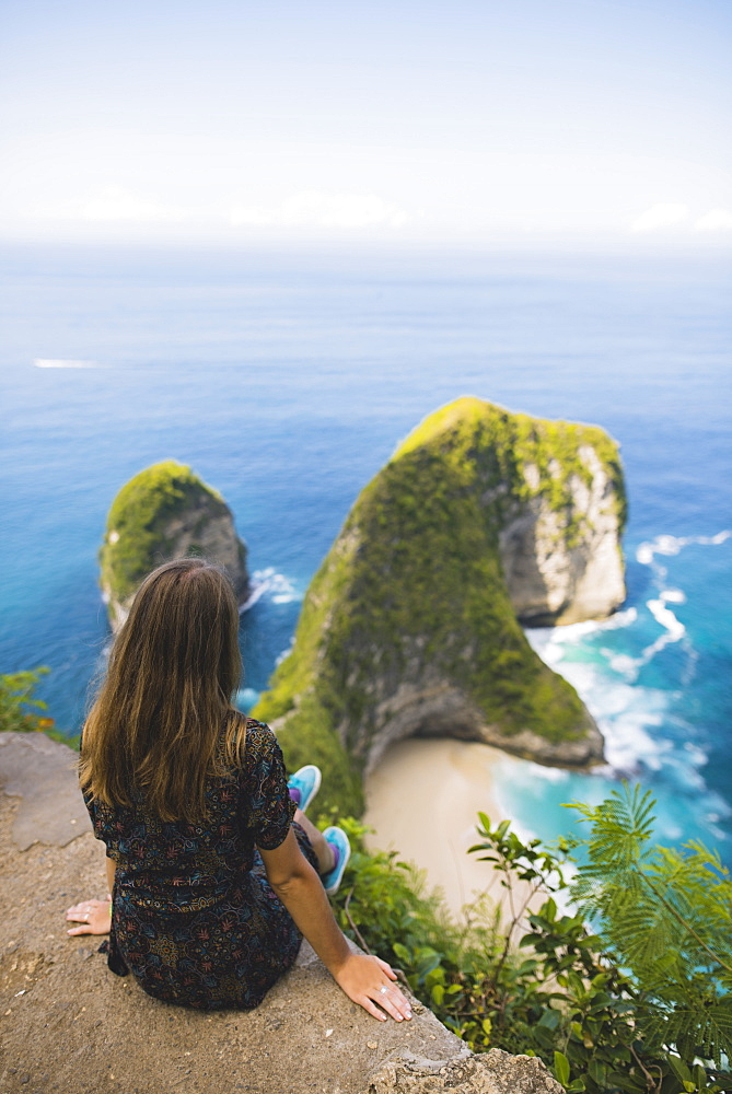 Woman sitting above Kelingking Beach in Nusa Penida, Indonesia