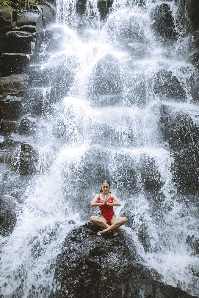 Woman wearing red swimsuit sitting by waterfall in Bali, Indonesia