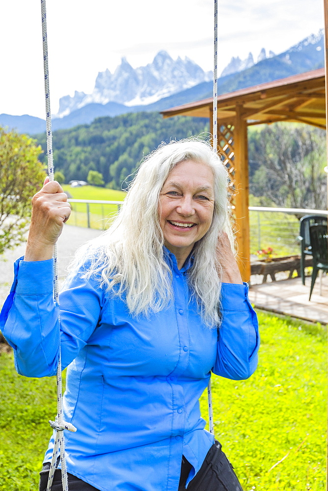 Mature woman smiling on swing, St. Peter, South Tyrol, Italy