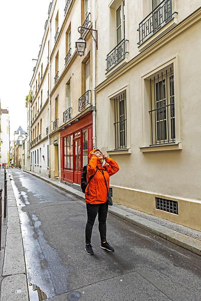 Woman wearing raincoat on street in Paris, France