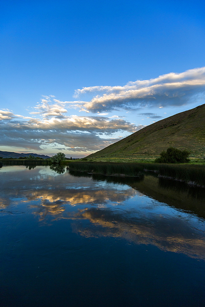 Lake by hill at sunset in Picabo, Idaho, USA