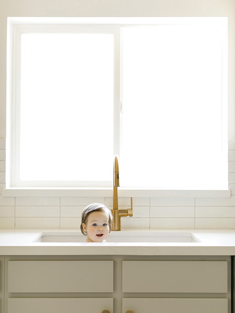 Baby girl bathing in kitchen sink