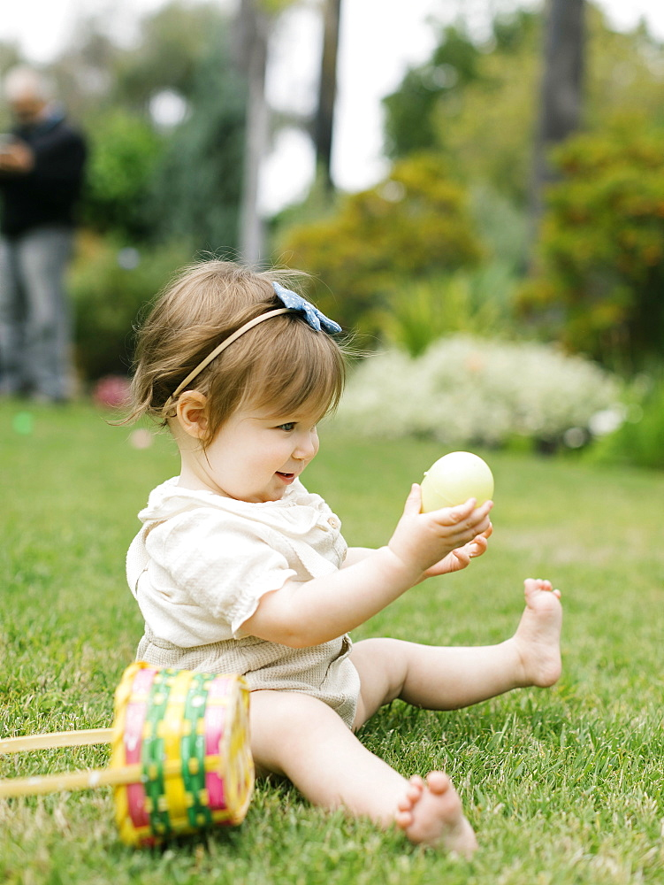 Baby girl with Easter egg and basket in back yard