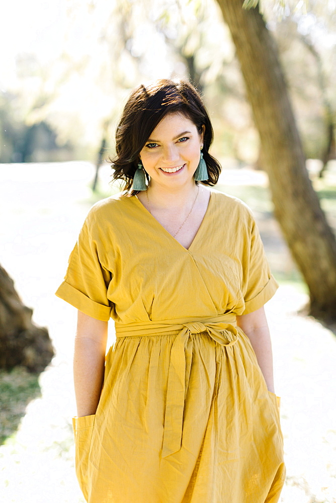 Smiling woman wearing yellow dress in park