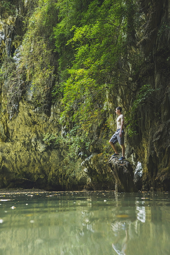 Shirtless man standing on rock in lake by cliffs in Krabi, Thailand