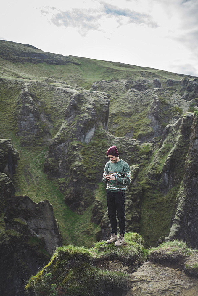 Man using smart phone on mountain in Kirkjubµjarklaustur, Iceland