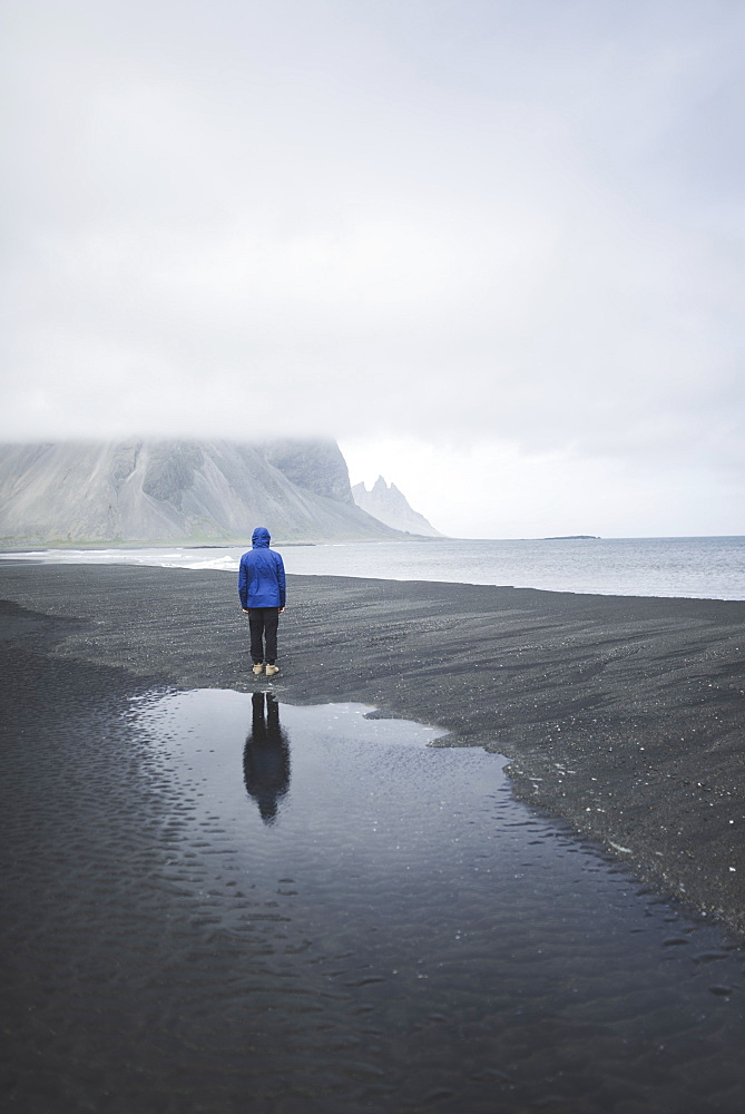 Man wearing blue coat on black sand beach in Kirkjubµjarklaustur, Iceland